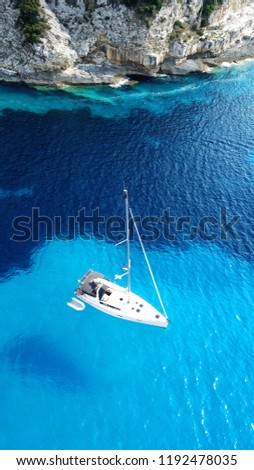 Aerial photo of iconic white cliff tropical bay forming a blue lagoon with deep turquoise clear ocean and docked luxury sail boats and yachts enjoying this unique paradise