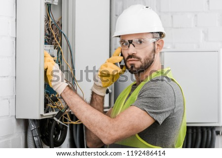 surprised electrician checking electrical box and talking by smartphone in corridor #1192486414