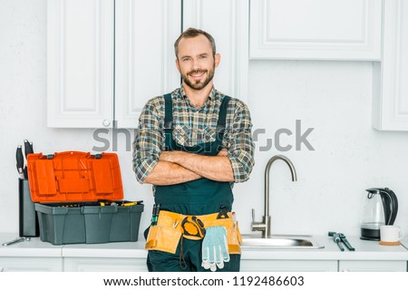 smiling handsome plumber standing with crossed arms and looking at camera in kitchen #1192486603