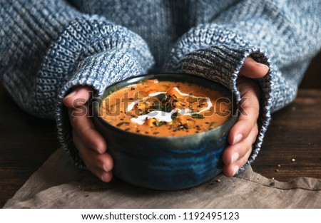 Female hands holding a bowl of pumpkin soup #1192495123