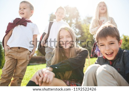 A group of happy smiling children sitting on the green grass in the park. The childhood, kids fashion, school, education, friends, lifestyle concept #1192522426