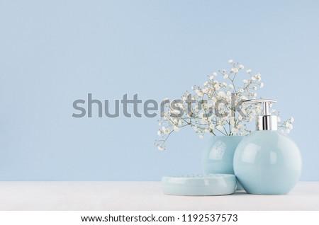 Light pastel blue ceramic acessories for bath  - bowl, vase, soap dispenser, flowers on white wood table. Decor for bathroom interior. #1192537573