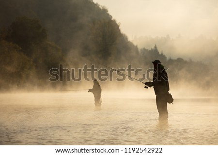 Men fishing in river with fly rod during summer morning. Beautiful fog. Royalty-Free Stock Photo #1192542922