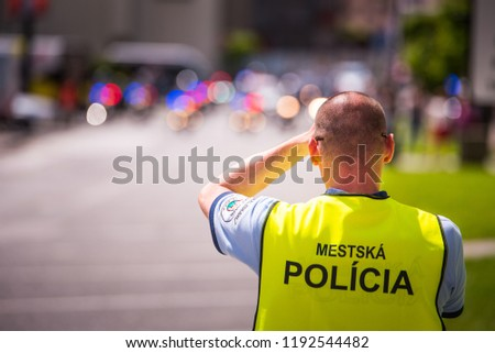 """Policeman in jacket with tittle """"Slovak Police"""" standing on the street."""
