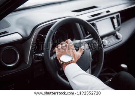 A young man sits in a newly bought car holding his hands on a rudder. #1192552720
