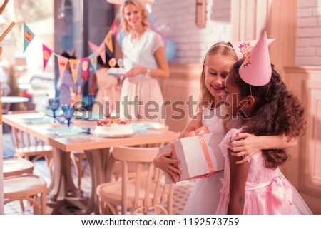 Girl friendship. Pretty little girl holding a big present and smiling while kindly hugging her best friend #1192573759