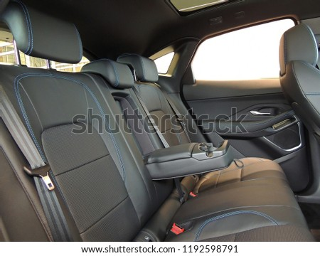 Leather trimmed folding armrest with cup holders in rear seats inside a vehicle  #1192598791