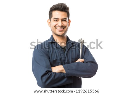 Smiling auto mechanic with wrench standing hands folded on white background #1192615366