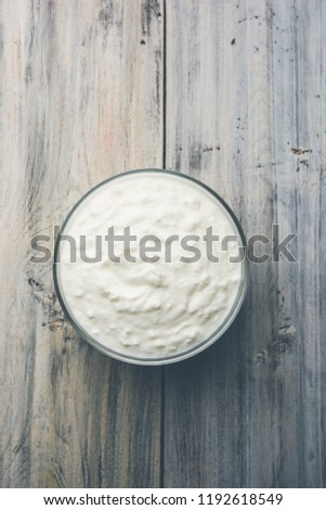 Plain curd or yogurt or Dahi in Hindi, served in a bowl over moody background. Selective focus #1192618549