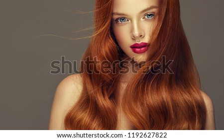 Young, red haired woman with voluminous hair.Beautiful model with long, dense, curly hairstyle .