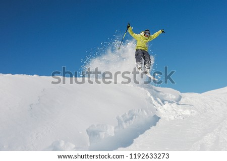Active skier dressed in bright yellow sportswear riding down the mountain slope in Georgia, Gudauri on sunny day #1192633273