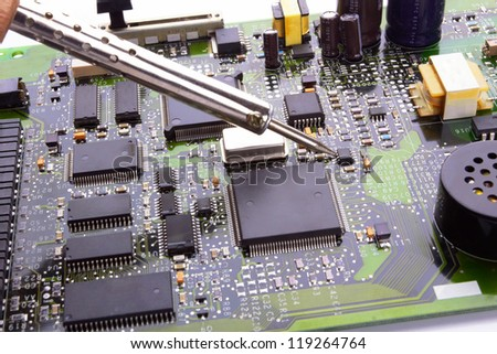 computer micro circuit board with iron soldering and tin wire in electronic laboratory #119264764