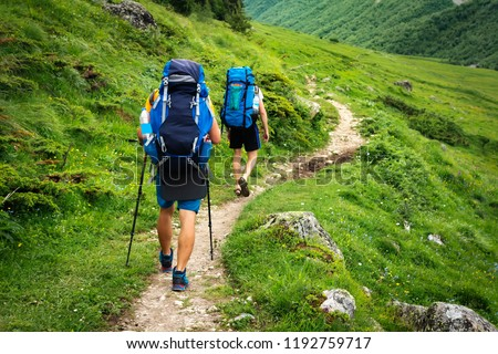 Hiking trail in Svaneti region, Georgia. Two hikers men walk on trek in mountain. Tourists with backpacks hike in highlands. Trekking in mountains. Hills and mounts in sport tourism. #1192759717