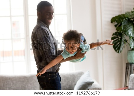 African American family spend time together have a fun standing in living room at home. Laughing father holding on hands flying smiling cute little preschool toddler son. Happy black family concept #1192766179