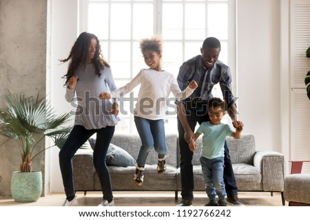 Full length black African whole family have a fun. Married couple with little kids toddler son preschool daughter dancing moving in living room at new home. Happy family spend time together concept #1192766242