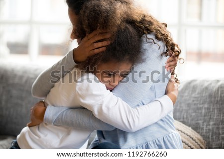 Black African mother embrace little preschool frustrated kid sitting on couch together at home. American loving mother supports disappointed daughter sympathizing, making peace after scolding concept #1192766260