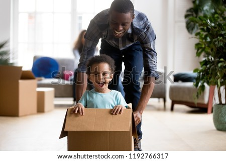 Black family in living room have a fun spend time at new home. African adorable playful laughing boy sitting at cardboard box, father rolling him playing together. New property and relocation concept #1192766317