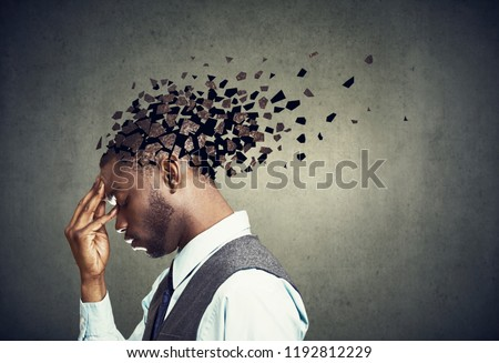 Memory loss due to dementia or brain damage. Side profile of a sad man losing parts of head as symbol of decreased mind function. #1192812229