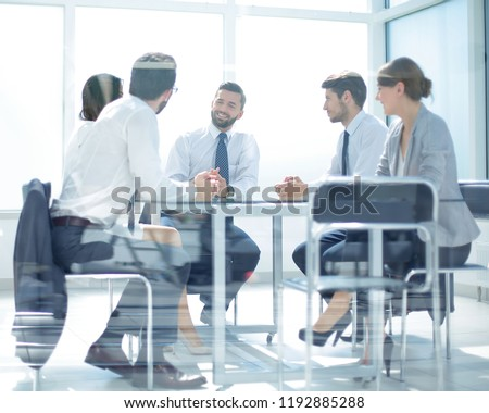 hrough the glass.the business team is holding a meeting #1192885288