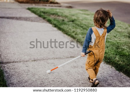 Blind or Visually Impaired Child/Kid/Toddler/Preschooler/Boy Walking Through Neighborhood with Long White Cane; Back to Camera (Copy Space) #1192950880