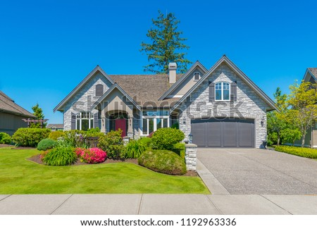 Big custom made luxury house with nicely landscaped and trimmed front yard and driveway to garage in the suburbs of Vancouver, Canada. #1192963336