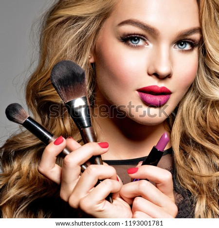 Beautiful woman holds cosmetic tools. Makeup. Beauty concept. Pretty girl with long curly hair.  Fashion make-up.  Closeup portrait. Gorgeous face of an attractive fashion model. Bright red lips. #1193001781