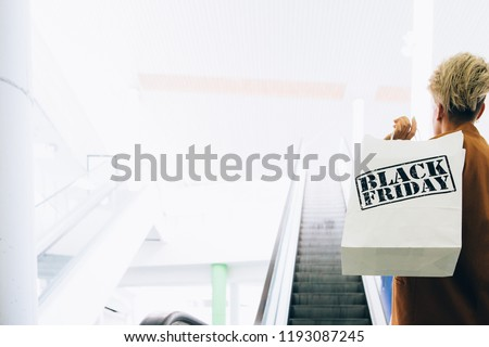 Black Friday. Back view of a girl holds paper shopping bags near an escalator in a mall. Indoor shoot. Copy space area available. #1193087245