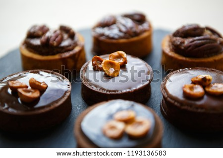 Delicious chocolate cakes with nuts and cocoa icing for lunch in cafe.Tasty little cake with nut on topping for dinner served on plate in restaurant.Enjoy sweet dessert food with natural ingredients #1193136583