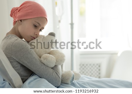 Weak girl with cancer wearing pink headscarf and hugging teddy bear  #1193216932