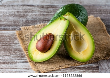 Close-up of an avocado and avocado oil on wooden table. Healthy food concept. #1193222866