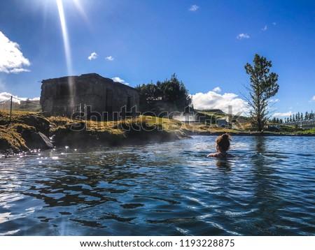 Woman swimming in natural thermal pool in fludir secret lagoon #1193228875