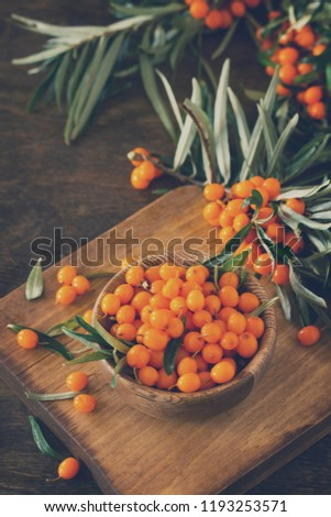 Fresh sea buckthorn berries in a wooden bowl on a rustic background. Copy space. Toned image. #1193253571