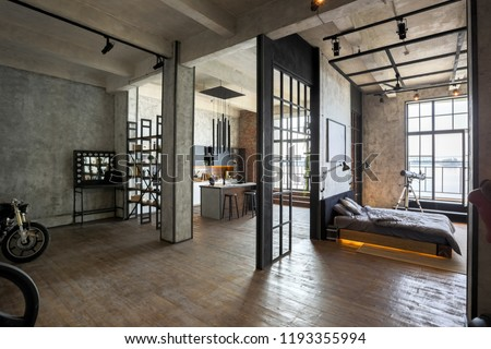luxury studio apartment with a free layout in a loft style in dark colors. Stylish modern kitchen area with an island, cozy bedroom area with fireplace and personal gym #1193355994
