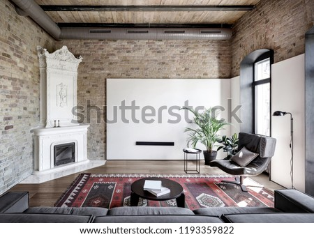Hall in a loft style with brick walls, wooden ceiling and a parquet with a carpet on the floor. There is a gray sofa, round table with books, stand, armchair, white fancy fireplace, plants, windows. #1193359822