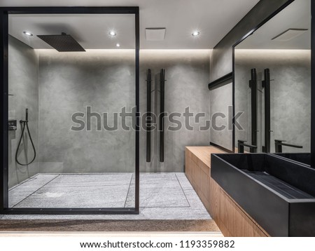 Bathroom in a modern style with gray tiled walls. There is a shower with a glass partition, wooden stand with a black sink and a faucet, large mirror, luminous lamps. Horizontal. Royalty-Free Stock Photo #1193359882