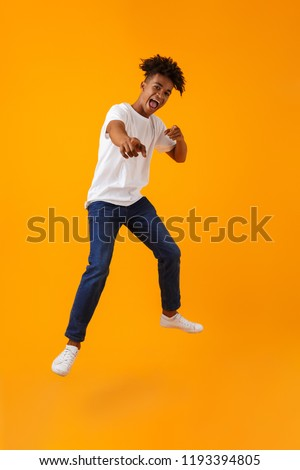 Image of happy young african man jumping isolated over yellow background pointing to you. #1193394805