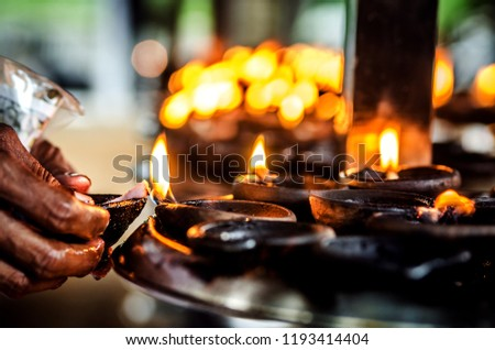 The believer lights a candle in a Buddhist temple. Sri Lanka.  #1193414404