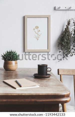 Stylish interior design of kitchen space with small table with mock up frame, herbs, cups of tea and notebooks. Minimalistic interior.