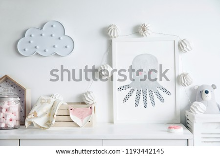 Stylish scandinavian newborn baby room with toys, teddy bears, wooden boxes and cloud. Modern interior with mock up photo frame and childs accessories. #1193442145