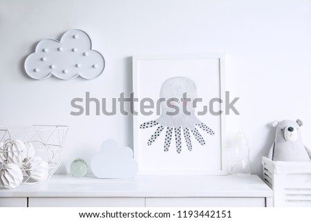 Stylish scandinavian newborn baby shelf with mock up photo frame, box, teddy bear and toys. Modern interior with white walls and wooden accessories. #1193442151