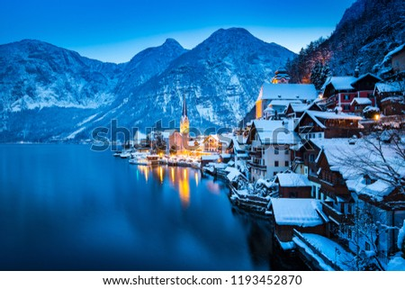 Classic postcard view of famous Hallstatt lakeside town in the Alps with beautiful Hallstattersee in mystical post sunset twilight during blue hour at dusk in winter, Salzkammergut, Austria #1193452870