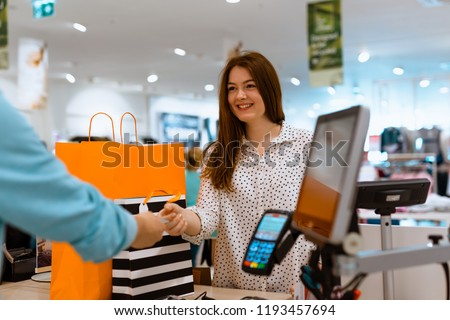 Woman paying for apparel in store Royalty-Free Stock Photo #1193457694