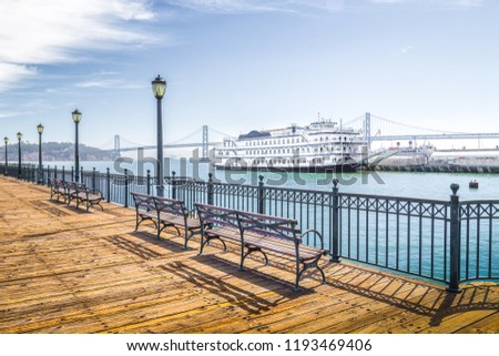 Benches at historic Pier 7 with traditional paddleboat and Oakland Bay Bridge in the background on a sunny day with bliue sky and clouds, San Francisco, California, USA #1193469406