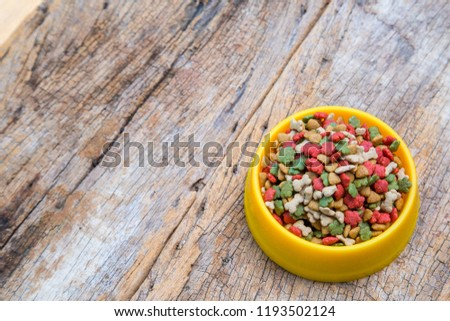 Top view of dry dog food in bowl on wooden background. #1193502124