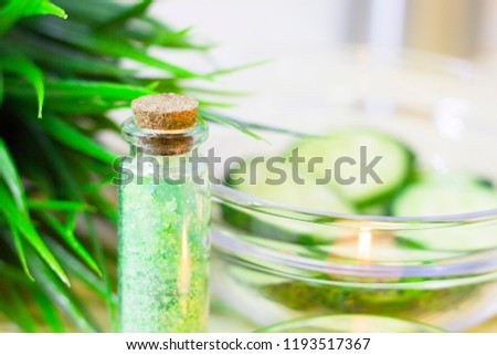 Cucumber home spa and hair care concept. Sliced cucumber, bottles of oil, bathroom towel. Straw light background. Closeup #1193517367
