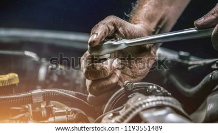 Auto mechanic working on car engine in mechanics garage. Repair service. authentic close-up shot Royalty-Free Stock Photo #1193551489
