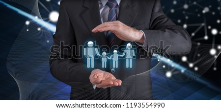 Family insurance concept with businessman in a protective gesture #1193554990
