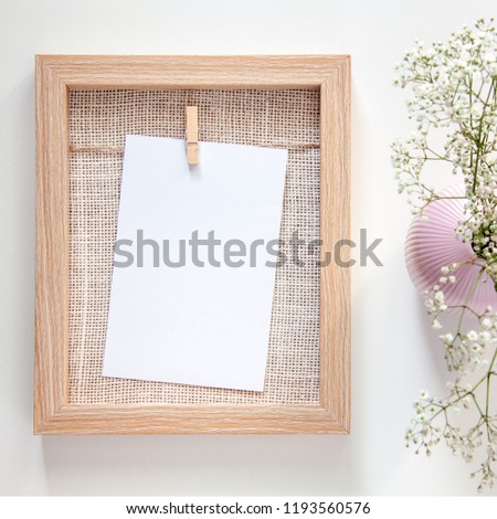 A wooden mockup frame with a white card and a pink vase with field dried flowers