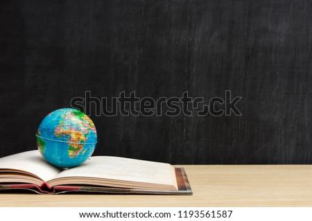 World globe on text book with blackboard background. Graduate study abroad programs.  International education school Concept. #1193561587