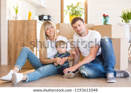 Portrait of the excited family about moving into new house. Happy parents and their blond toddler son are sitting on the floor at the background of cardboard boxes #1193611048